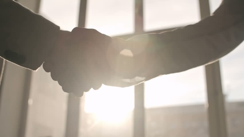 Close-up of two businessmen shaking hands in sunlight, backlit shot on Sony NEX 700