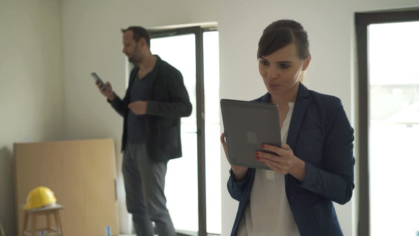Woman with tablet looking around her new home, male architect checking apartment  #16807633