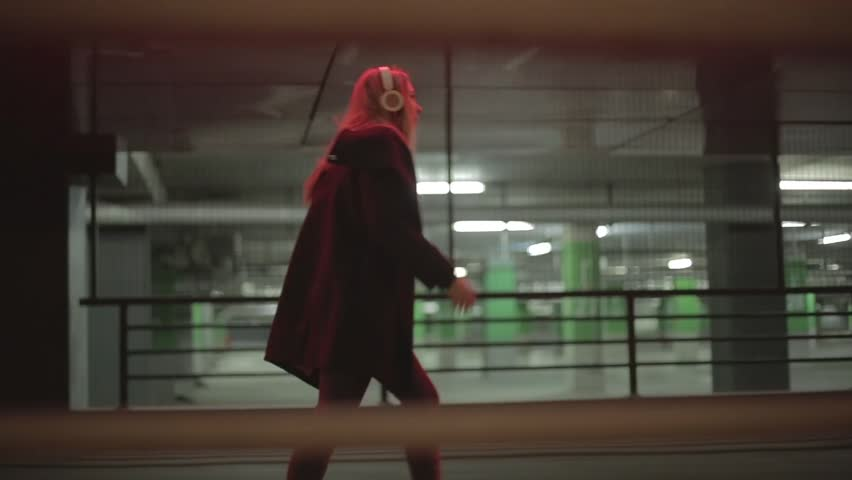 Teenage girl with long blonde hair walking fast along the street,listening to the music,wearing headphones at night under red lights, wearing black coat, jeans and high heel boots.  | Shutterstock HD Video #16808032