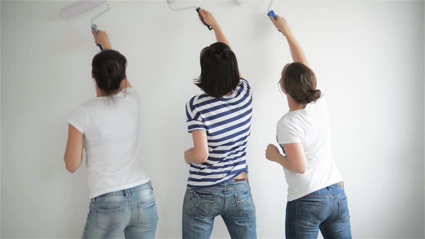 Friends makes repairs at home. Funny girls dance and paint the walls in the flat, good mood, making repairs and dance #16844416