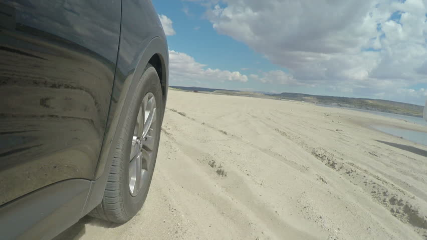 Tire View Driving Through Sand Beach. car driving on the beach during summer time. Low angle view of the tire  | Shutterstock HD Video #16873525