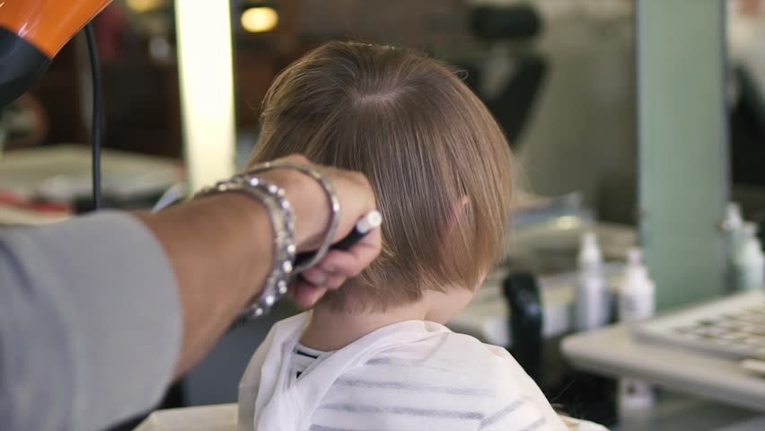 Hairdresser doing hair the little girl with a hair dryer. Close up. | Shutterstock HD Video #16885177