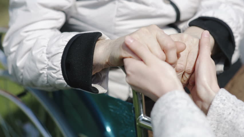 Caring young support girl holding the hand of elderly woman in a wheelchair
