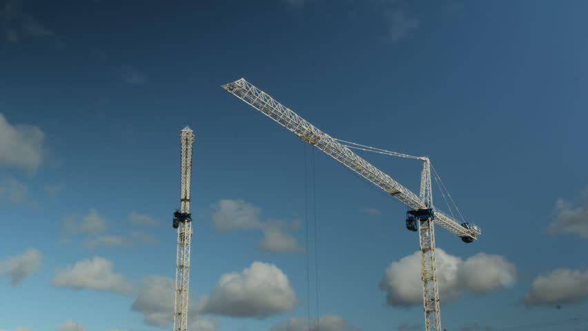 Two cranes. Timelapse. White tower cranes against blue sky. Timelapse shotClip is assembled from hi-res stills taken with a Canon 550D camera. Wideshot. Timelapse. Construction in Toronto.