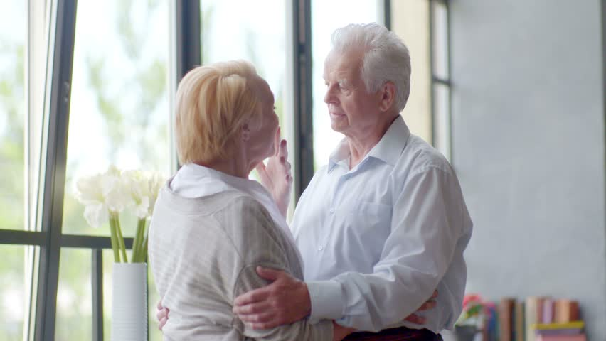 Loving and happy elderly couple cuddling and talking in modern apartment. husband looking at camera | Shutterstock HD Video #16900828