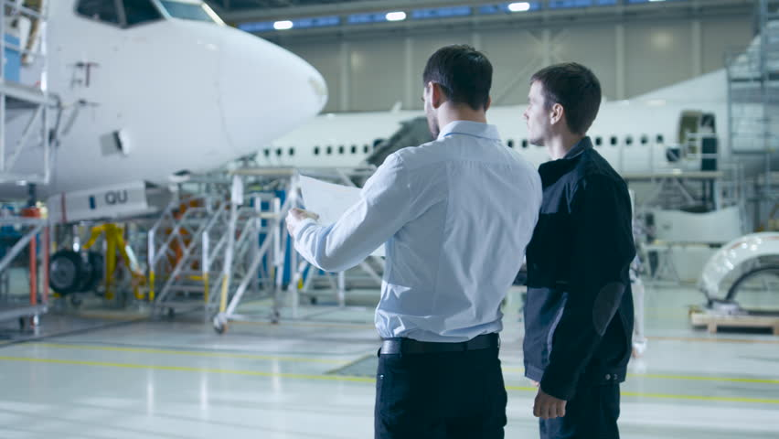 Aircraft Maintenance Worker and Engineer Having Conversation. Looking at the airplane.  | Shutterstock HD Video #16916095