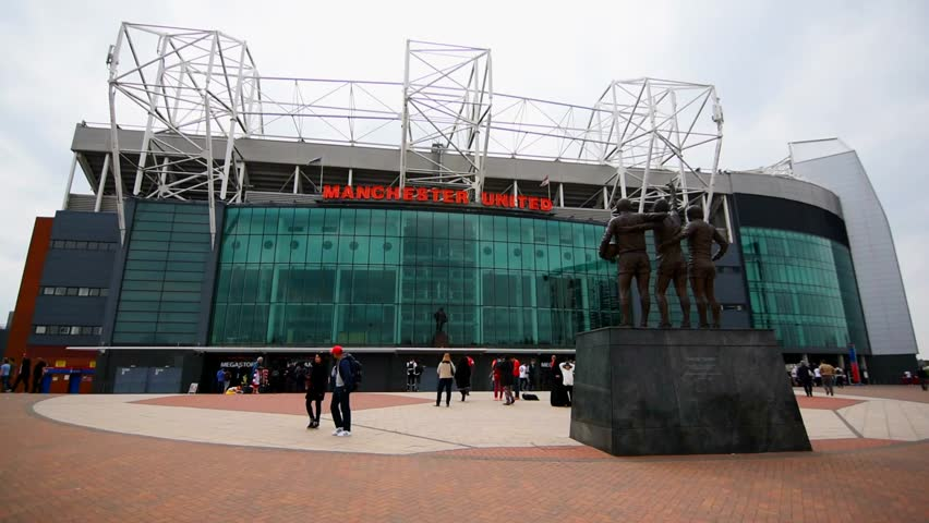 MANCHESTER, UNITED KINGDOM -28 MAY 2016: The entrance of the Old Trafford stadium with some tourists. Old Trafford is the home stadium of Manchester United Football Club since 1910.