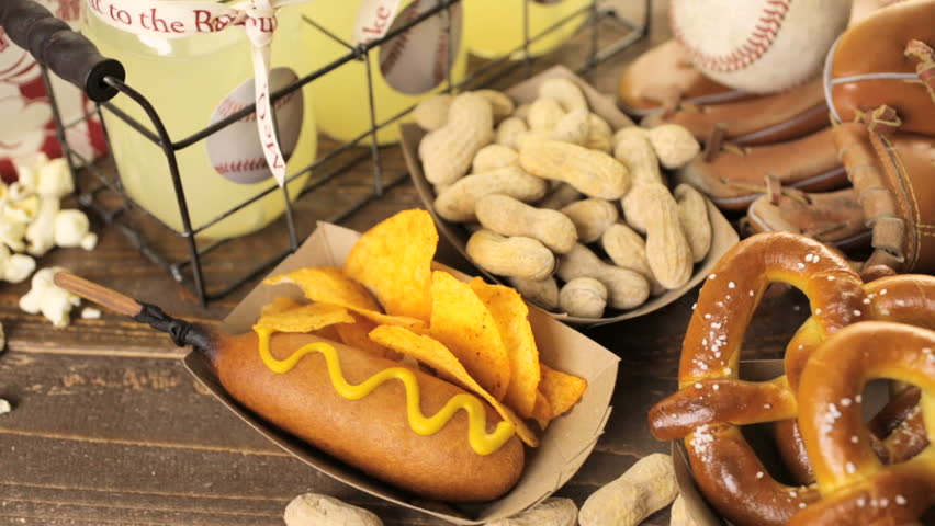 Game day traditional snacks included corndogs and salted peanuts on a wood board. | Shutterstock HD Video #16928407