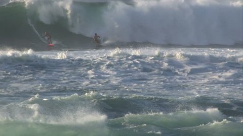 Surfer in a wave on Waimea Bay, North shore, Oahu Hawaii. Wave curling into a pipeline look. Beautiful blue azure water. Breaker with white splash.