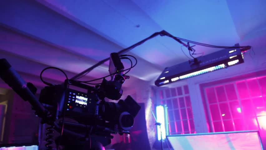 Professional videocamera with display, lamp and reflecting screen in dark room #1694977