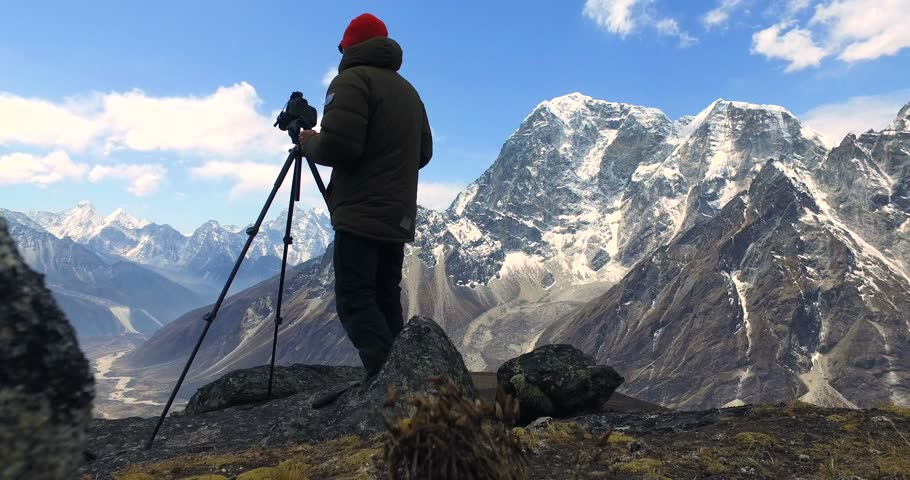 Man makes photos, in the mountains of Nepal. Photo tour to the base camp of Mount Everest. Ama Dablam view, from Awi peak, 5200 m). Awi peak is a part of Everest Base Camp trek. #16980283