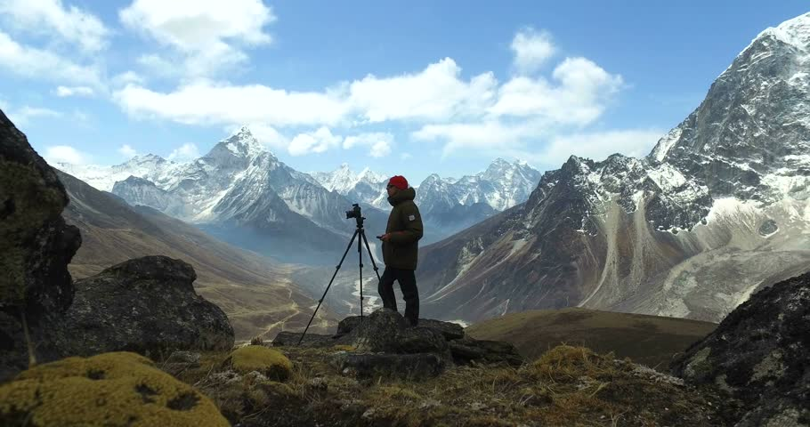 Man makes photos, in the mountains of Nepal. Photo tour to the base camp of Mount Everest. Ama Dablam view, from Awi peak, 5200 m). Awi peak is a part of Everest Base Camp trek. #16980286