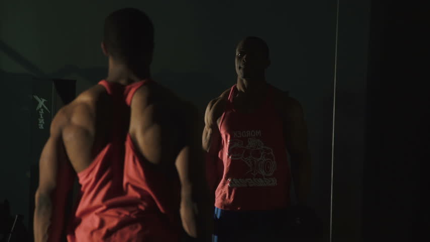 Black muscular african-american weight lifter training at the gym and looks on mirror reflection on dark background  #16981138