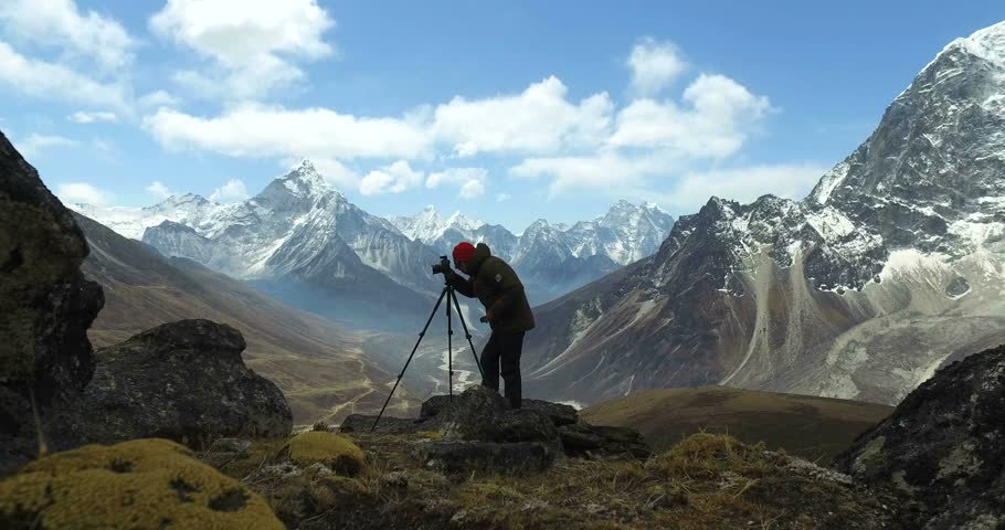Man makes photos, in the mountains of Nepal. Photo tour to the base camp of Mount Everest. Ama Dablam view, from Awi peak, 5200 m). Awi peak is a part of Everest Base Camp trek. #16981150