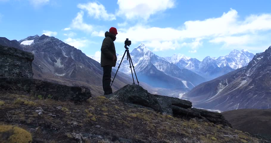 Man makes photos, in the mountains of Nepal. Photo tour to the base camp of Mount Everest. Ama Dablam view, from Awi peak, 5200 m). Awi peak is a part of Everest Base Camp trek. #16984702