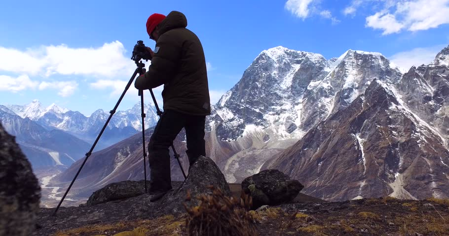 Man makes photos, in the mountains of Nepal. Photo tour to the base camp of Mount Everest. Ama Dablam view, from Awi peak, 5200 m). Awi peak is a part of Everest Base Camp trek. #16986229