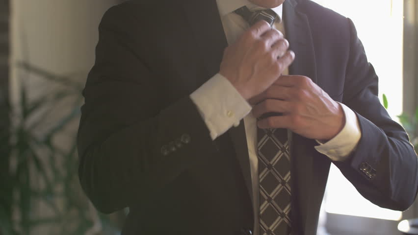 Elegant business man in white shirt correcting his tie and buttoning his suit jacket. close up