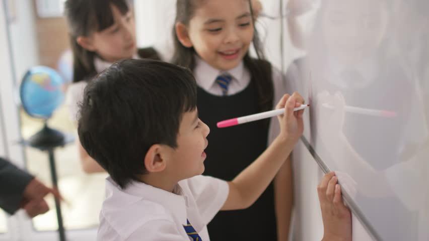 4K Happy school children in class writing on board with teacher UK - April, 2016 | Shutterstock HD Video #17024788