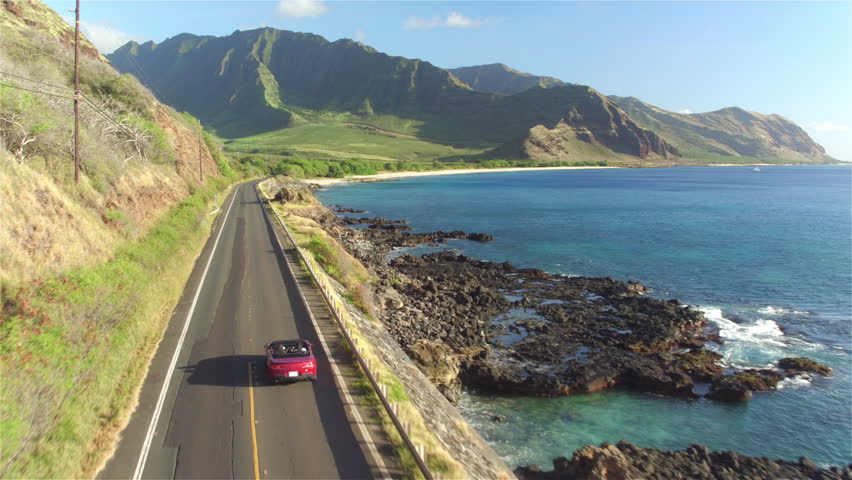 AERIAL: Red convertible car driving along the coastal road above dramatic rocky shore towards volcanic mountains. Happy young couple on summer vacation traveling at the seaside in Oahu island, Hawaii Royalty-Free Stock Footage #17029471