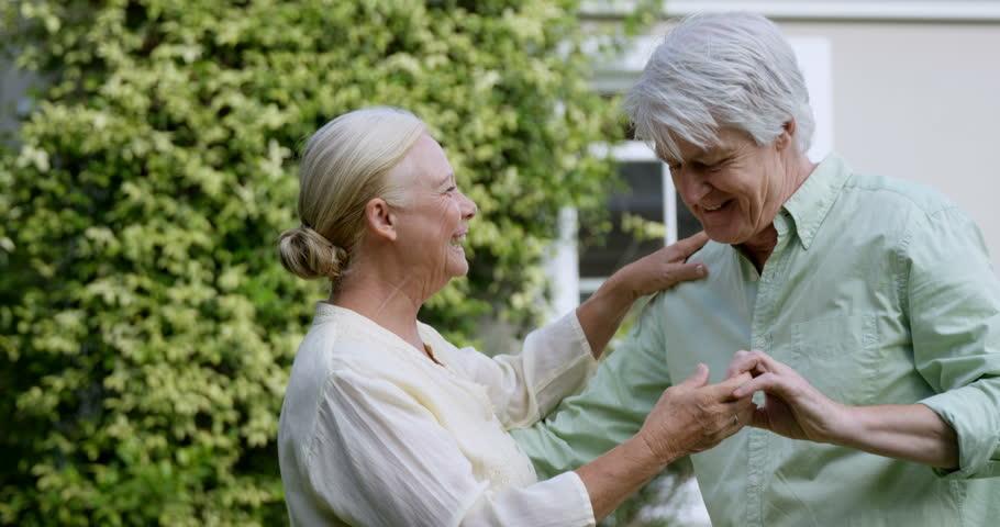 Lovely elder couple dancing in the garden