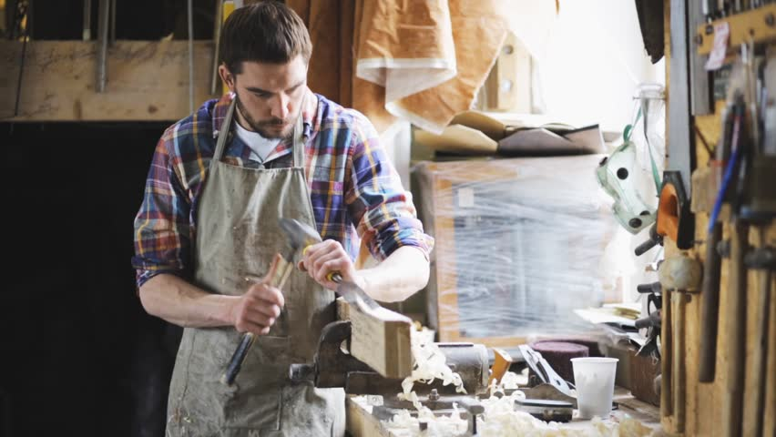 Profession, people, carpentry, woodwork and people concept - carpenter with hammer and chisel processing wood plank at workshop | Shutterstock HD Video #17040376