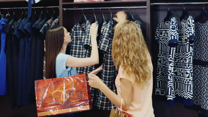 Two young women choosing clothes in a shop #17042008