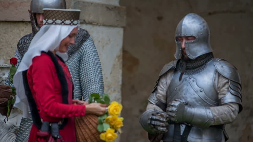 Princess is smiling and she is giving yellow roses to the knights who are about to go into a battle soon. Close-up shot.