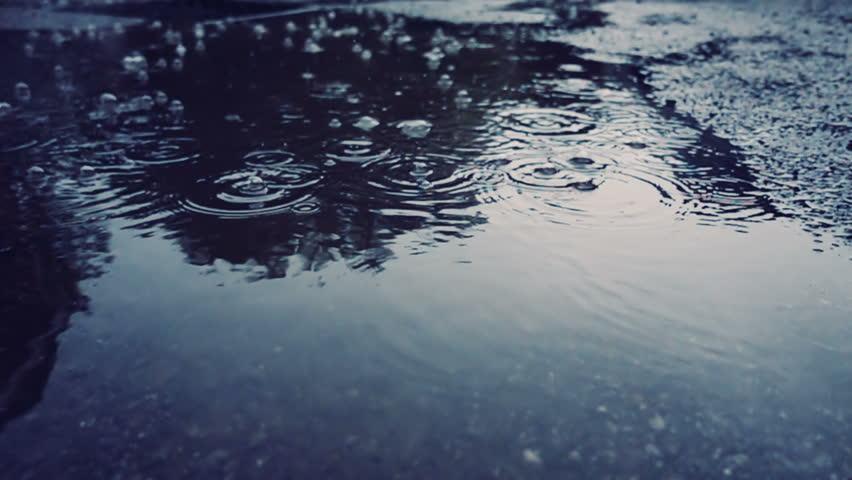 Rain falling on pavement in slow motion