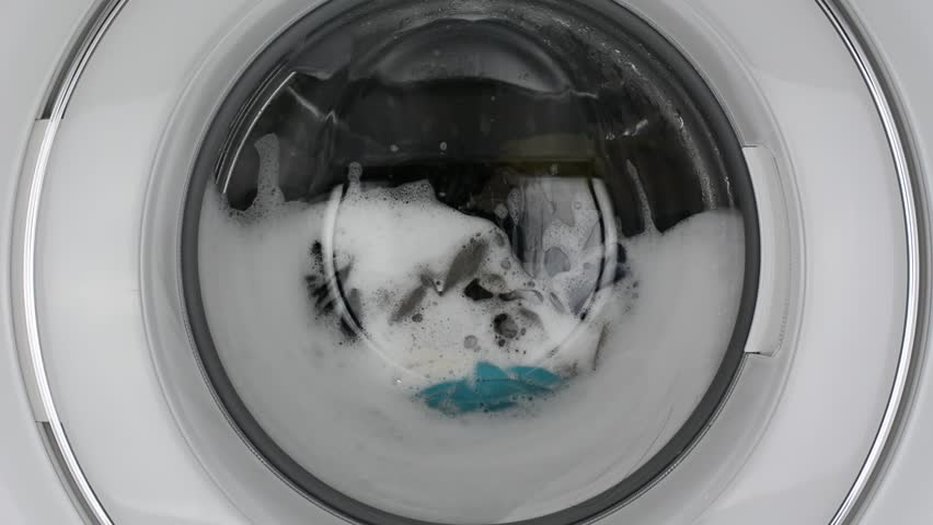 Washing machine washing clothes./ Washing clothes with laundry detergent.