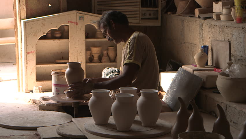 Pottery workshop. Pan-left on an Arab potter sitting on the floor in his workshop throwing a pot on a wheel. He is surrounded by finished clay pots. (Bahrain - 2015) | Shutterstock HD Video #17160742