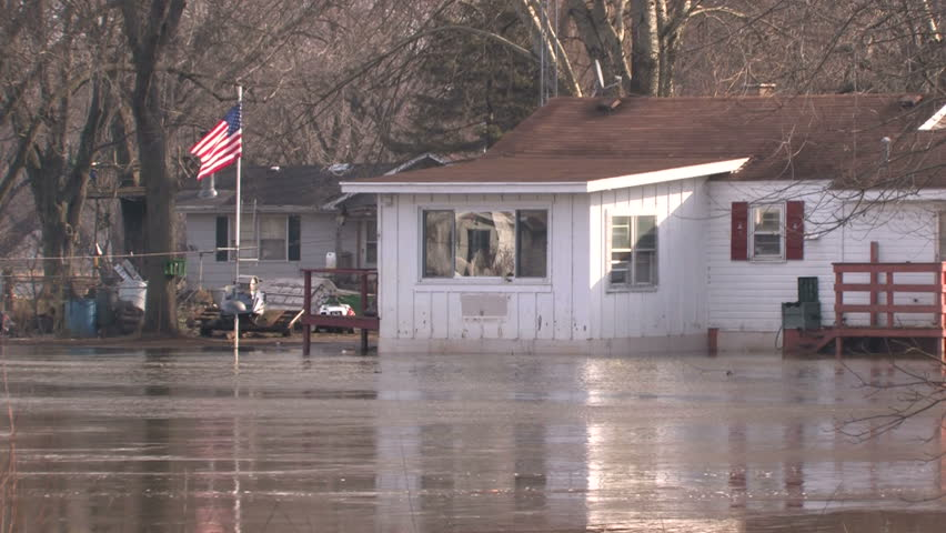 Floodwater flows around a small house with an American flag