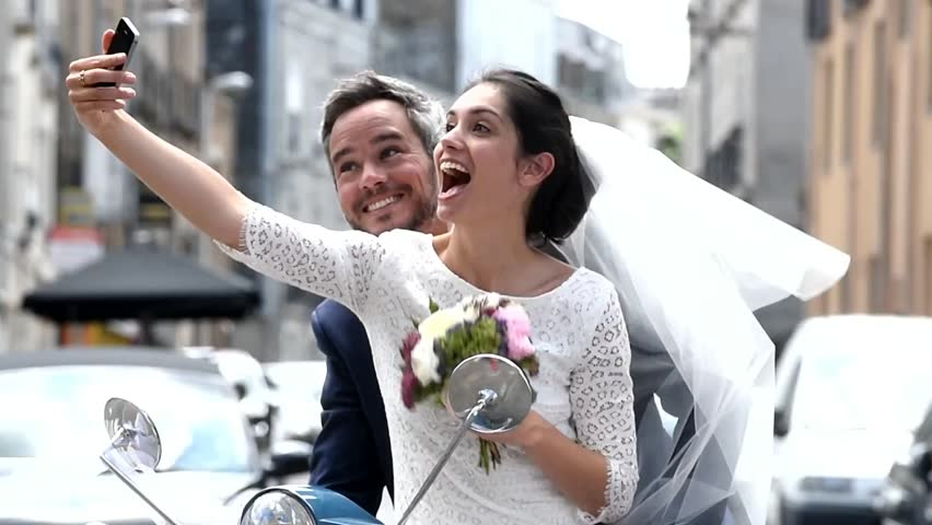 Cheerful newlywed couple having fun on a scooter, they are making selfies with a smartphone before to leave for their honeymoon #17207656
