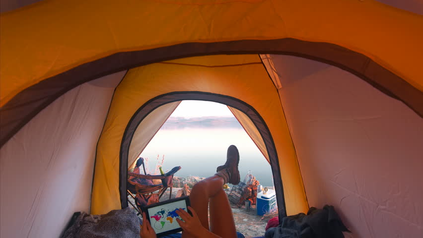 4k Medium shot of epic young traveler woman using a tablet to view a world map whilst chilling in her tent on camping adventure.