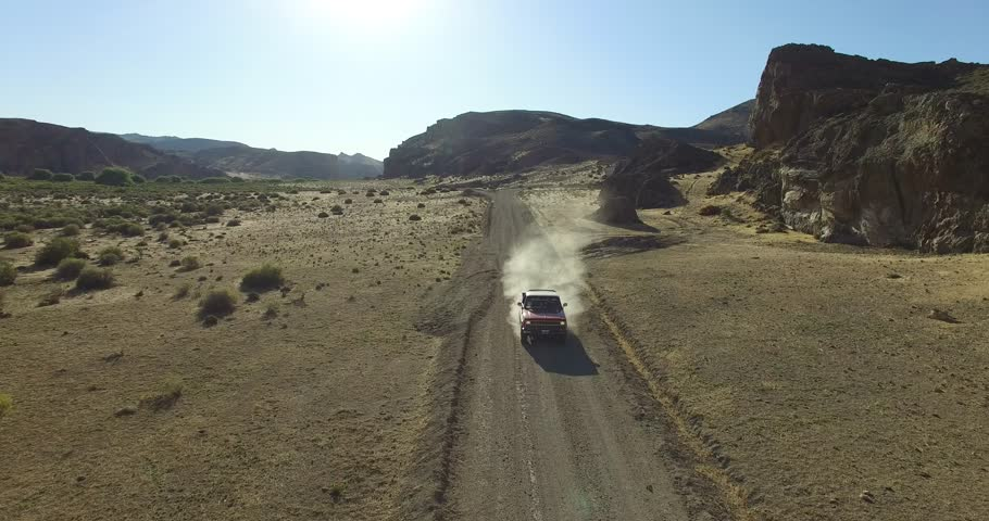 Aerial scene of car traveling on dirt road a dry, rocky, landscape. Monumental scenery. Car leves dust while driving. Canyon of Piedra Parada, Chubut, Patagonia Argentina. Hiking place.