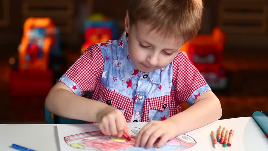 Beautiful Boy Paints the Car With Crayons Sitting at Table at Home #17240422