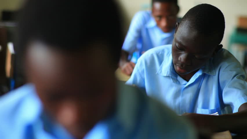 KENYA, AFRICA - CIRCA 2011: Shot of a school boy reading his book in class, then looking up, in Kenya, Africa.