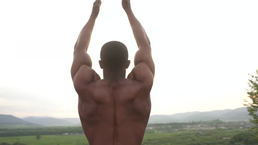 Close-up of african american body builder with prayer hands stretching on the mountain peak during his morning outdoor training. Sunrise sky background, camera movement #17251489