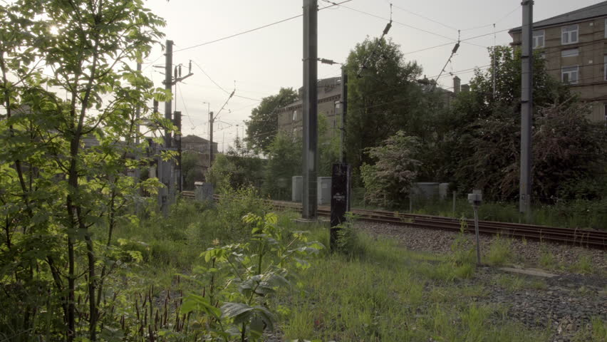 Urban town decay establishing shot UHD stock footage. Weeds left to overgrow in an unkept part of town depicting urban decay. #17263411