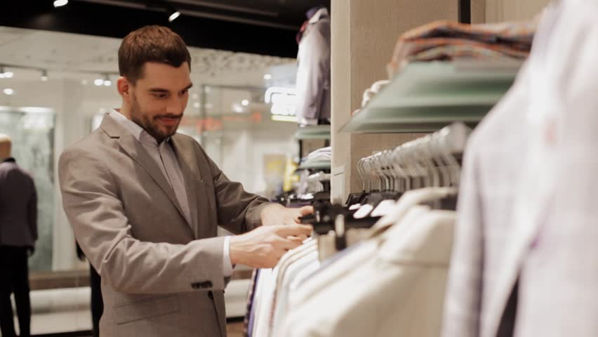 Sale, shopping, fashion, style and people concept - elegant young man in suit choosing clothes in mall or clothing store | Shutterstock HD Video #17281435