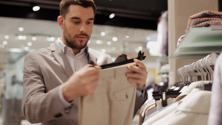 Sale, shopping, fashion, style and people concept - elegant young man in suit choosing clothes in mall or clothing store | Shutterstock HD Video #17281441