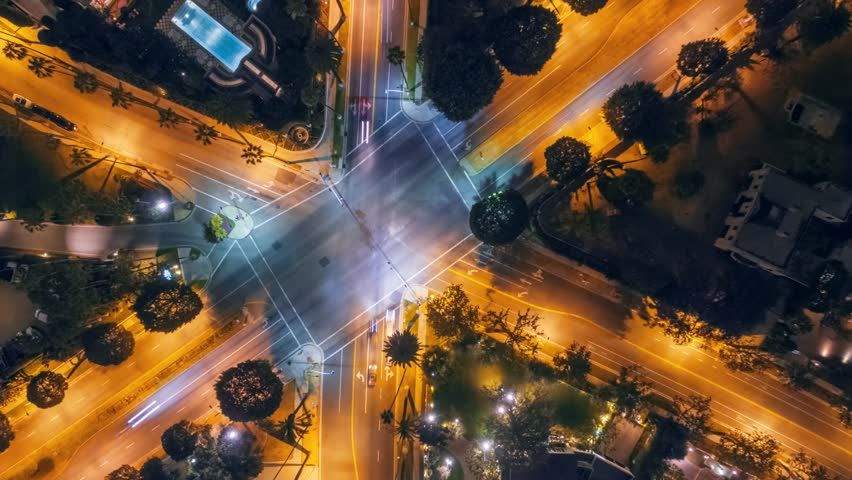 Timelapse of night city traffic on three street intersection in Beverly Hills, CA. 4K UHD vertical aerial view.