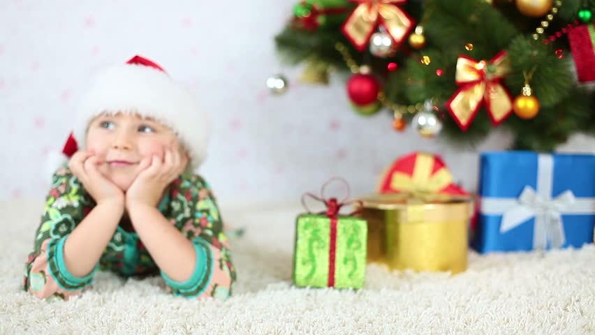 Smiling girl in Santa hat lying near the Christmas Tree