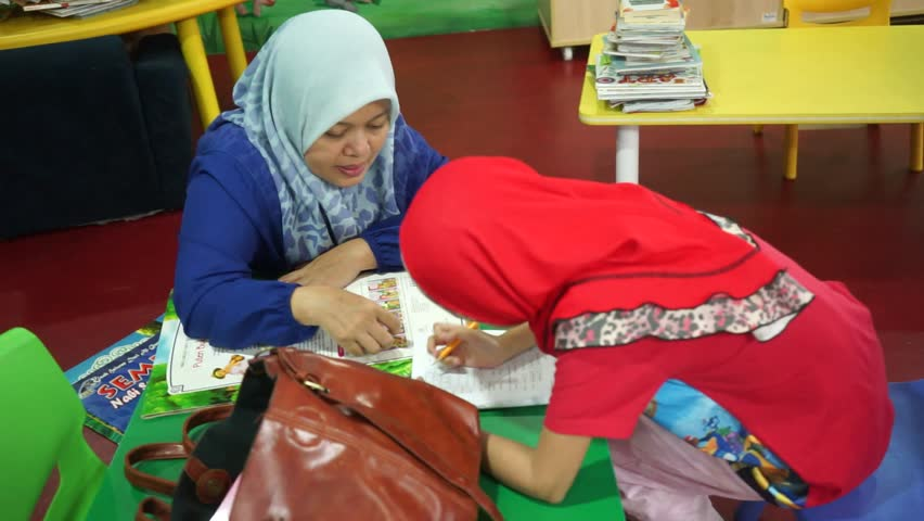 Asian Muslim mom wearing headscarf helping kids reading books, and finishing homework in a children library corner. Royalty-Free Stock Footage #17308993
