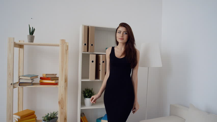 Sexy brunette business woman in fashionable black dress standing in light office #17312371