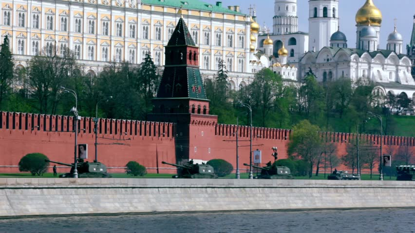 Tanks and other military hardware ride by quay of Moscow Kremlin, red brick walls and Ivan Great Bell Tower. Victory Day 1945 year. Russia.