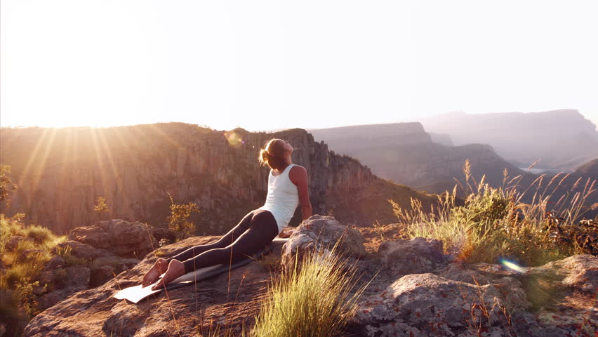 Healthy young independent female yoga practitioner, practicing meditation and poses on the top of epic mountain with beautiful serene view overlooking the pureness and oneness of nature. 4K. Raised | Shutterstock HD Video #17345083
