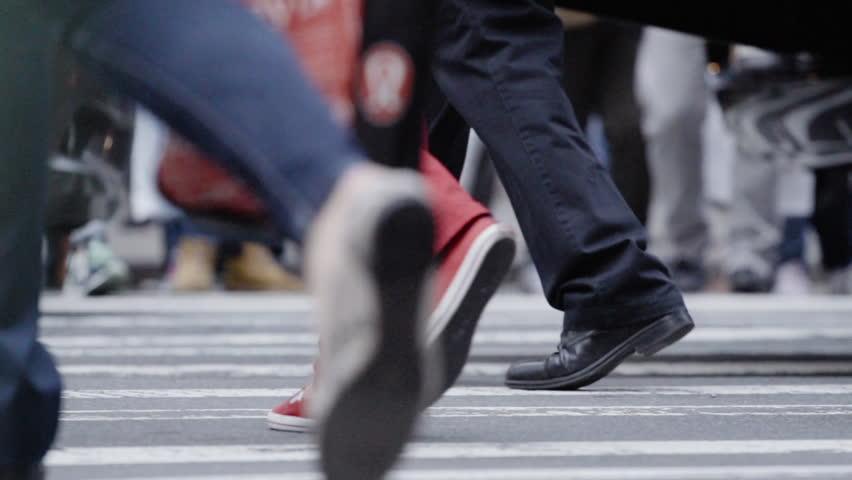 A close-up, slow motion establishing shot of a crowded New York City crosswalk. New York - May 23, 2016