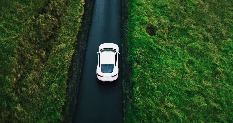 Aerial view electric car driving on country road, luxury car driving through mist at dusk with headlights | Shutterstock HD Video #17354431