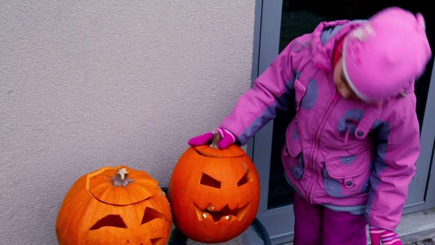 Little girl in pink jacket and cap watch on two Halloween pumpkin heads | Shutterstock HD Video #1738264
