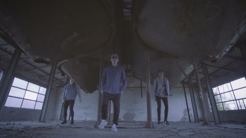 Video of active young group dancing choreography in an abandoned building.